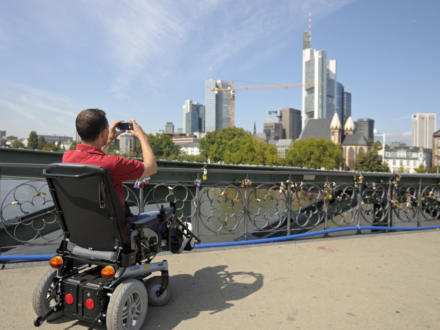 A wheelchair user on a bridge, taking a photo of the Frankfurt skyline.